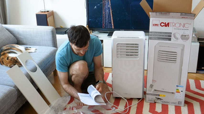 eenheid : Paris, France - Circa 2019: Young man being helped by his cat unboxing installing new portable air conditioner unit AC during hot summer in his living room inspecting the device and all the accessories reading instruction manual Stockvideo