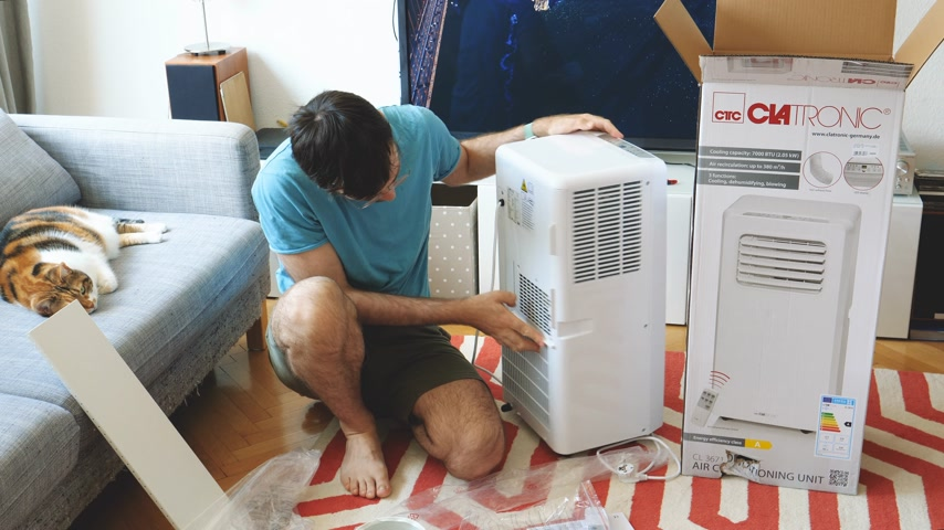 очиститель : Paris, France - Circa 2019: Young man being helped by his cat unboxing installing new portable air conditioner unit AC during hot summer in his living room inspection for scratches and bents Стоковые видеозаписи