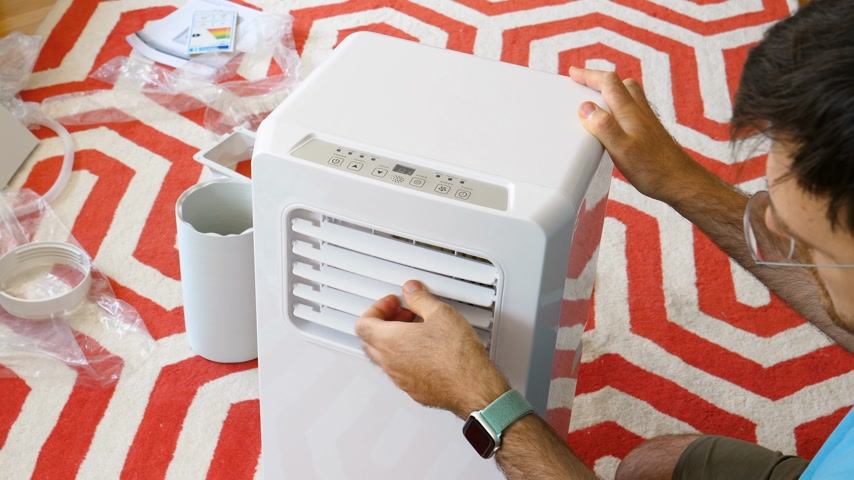 chladič : Paris, France - Circa 2019: Young man unboxing installing new portable air conditioner unit AC during hot summer in his living room learning the buttons and their functions
