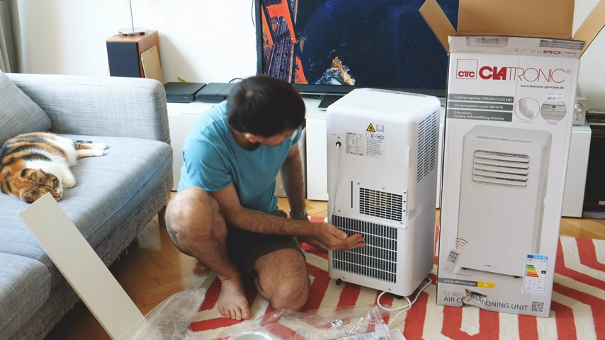 очиститель : Paris, France - Circa 2019: Young man being helped by his cat unboxing installing new portable air conditioner unit AC during hot summer in his living room inspecting the hepa filters and cables Стоковые видеозаписи