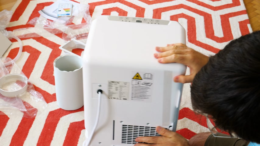 termostat : Paris, France - Circa 2019: Young man unboxing installing new portable Clatronic air conditioner unit AC during hot summer in his living room learning the buttons and their functions