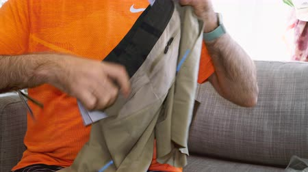 khaki : Paris, France - Circa 2019: Man unboxing unpacking new Nike professional running clothes apparel Nike Tech Pack Mens Running Shorts khaki color Stock Footage