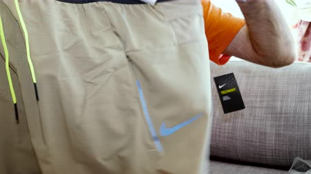 khaki : Paris, France - Circa 2019: Man unboxing unpacking new Nike professional running clothes apparel Nike Tech Pack Mens Running Shorts khaki color time lapse fast motion