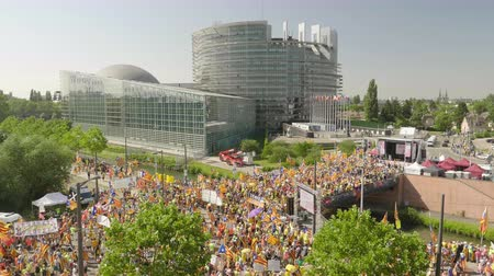 espana : Strasbourg, France - Jul 2 2019: Cinematic aerial view over thousands of people demonstrating at protest front of EU European Parliament against exclusion of three Catalan elected MEPs - drone view Stock Footage