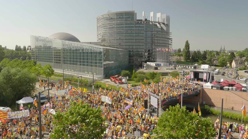választotta : Strasbourg, France - Jul 2 2019: Aerial view over thousands of people demonstrating at protest front of EU European Parliament against exclusion of three Catalan elected MEPs - drone view Stock mozgókép