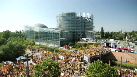 katalán : Strasbourg, France - Jul 2 2019: Slow motion aerial view over thousands of people demonstrating at protest front of EU European Parliament against exclusion of three Catalan elected MEPs - drone view