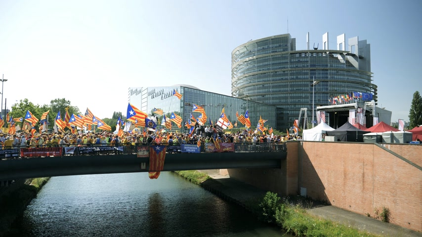 político : Strasbourg, France - Jul 2 2019: Slow motion People holding Estelada Catalan separatist flags demonstrating on bridge in front of EU European Parliament against exclusion of three Catalan elected MEPs