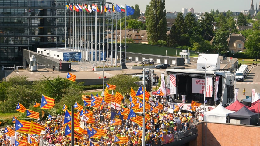 választotta : Strasbourg, France - Jul 2 2019: Drone view of Large group of people waving Estelada Catalan separatist flags demonstrate protest front of EU European Parliament against exclusion of three Catalan elected MEPs Stock mozgókép