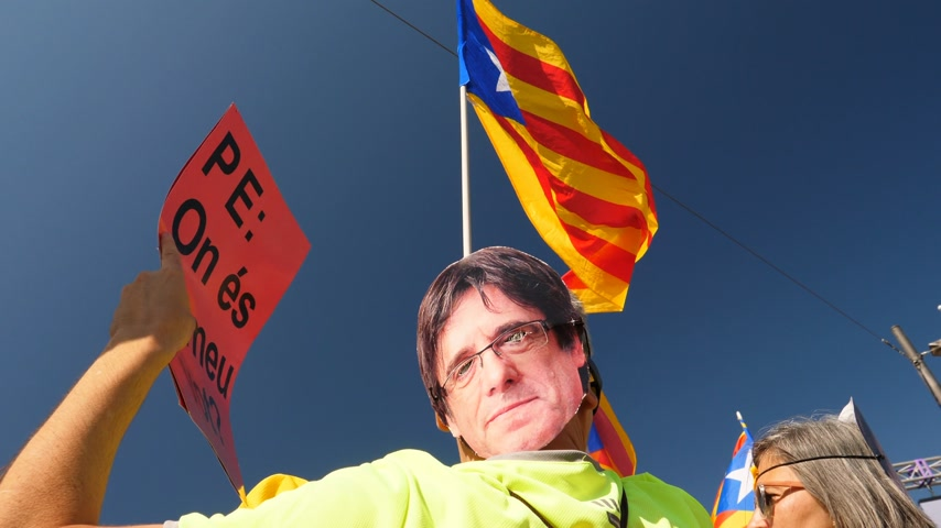 katalán : Strasbourg, France - Jul 2 2019: Man holding Estelada Catalan separatist flags wearing Carles Puigdemont mask at protest front of EU European Parliament against exclusion of three Catalan elected MEPs