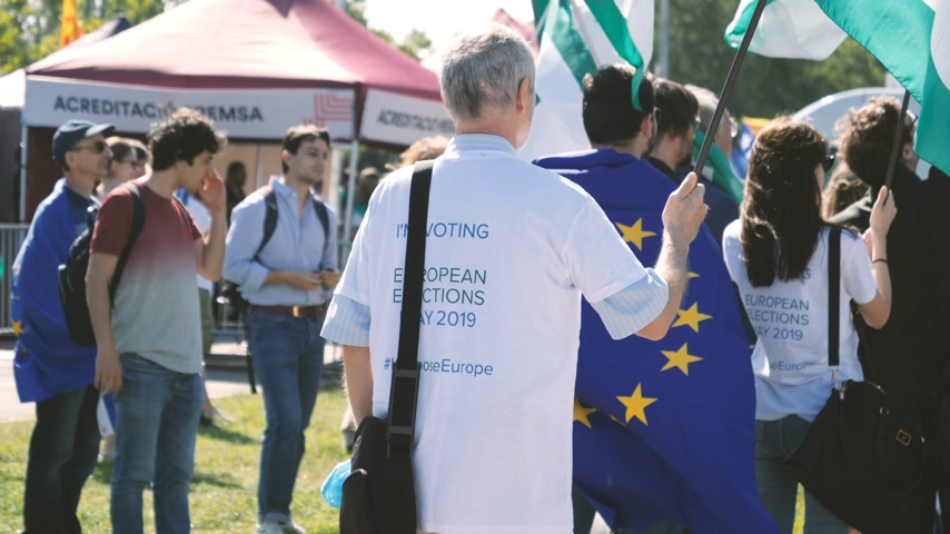 каталонский : Strasbourg, France - Jul 2 2019: Rear view Man holding Flag of the European Movement Federalist flag wearing Im voting at European Elections in may 2019 at protest in front of European Parliament - slow motion Стоковые видеозаписи