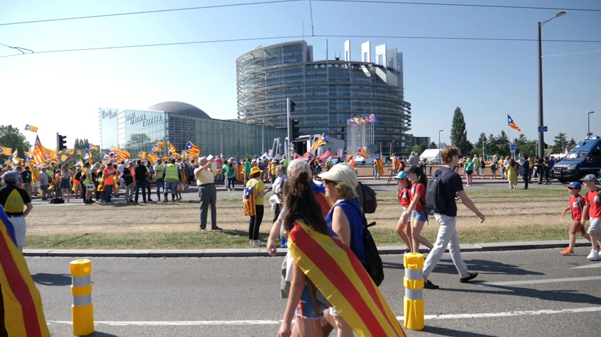 protestor : Strasbourg, France - Jul 2 2019: Group of senior people holding placards walking at demonstration protest front of EU European Parliament building against exclusion of Catalan elected MEPs slow motion