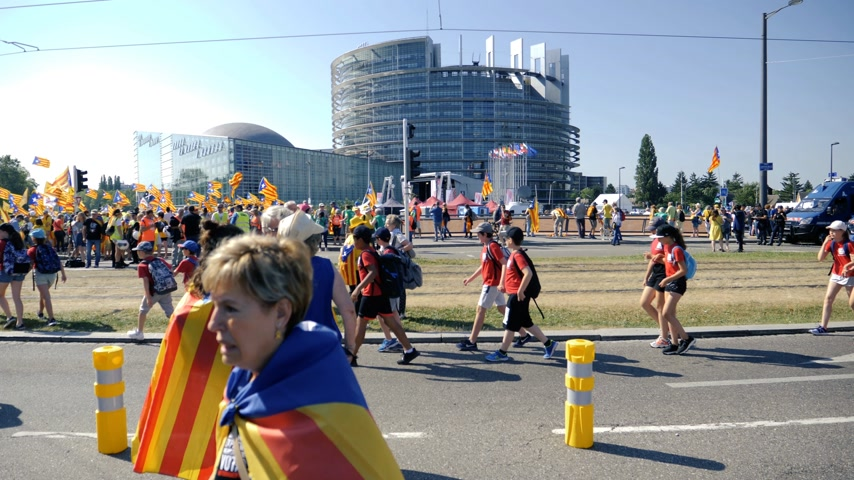 protestor : Strasbourg, France - Jul 2 2019: people holding placards walking at demonstration protest front of EU European Parliament building against exclusion of three Catalan elected MEPs slow motion