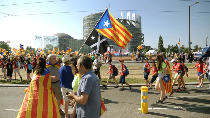 ралли : Strasbourg, France - Jul 2 2019: Side view of people holding placards walking at demonstration protest front of EU European Parliament building against exclusion of Catalan elected MEPs slow motion
