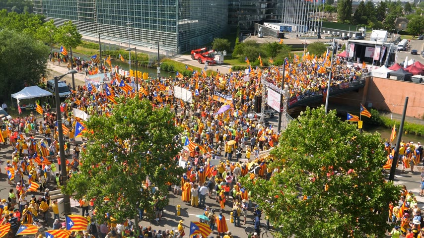 tilt : Strasbourg, France - Jul 2 2019: Tilt-up aerial view of people with Estelada separatist flags demonstrate protest at EU European Parliament against exclusion of Catalan elected MEPs Stock Footage