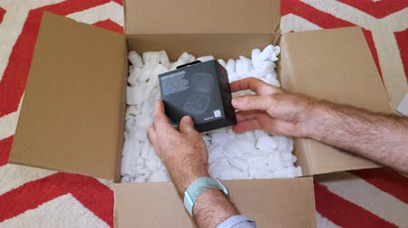 frágil : Paris, France - Circa 2019: Man hand unboxing unpacking the cardboard box with foam protection containing Apple Beats Powerbeats Pro headphones with surprise empty case - time lapse fast motion Vídeos
