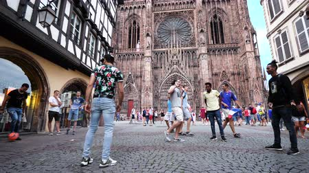 french team : STRASBOURG, FRANCE - JULY 15, 2018: Men playing soccer in front of Cathedral after victory of the French team in the final of the World Cup football in Russia against Croatia - slow motion