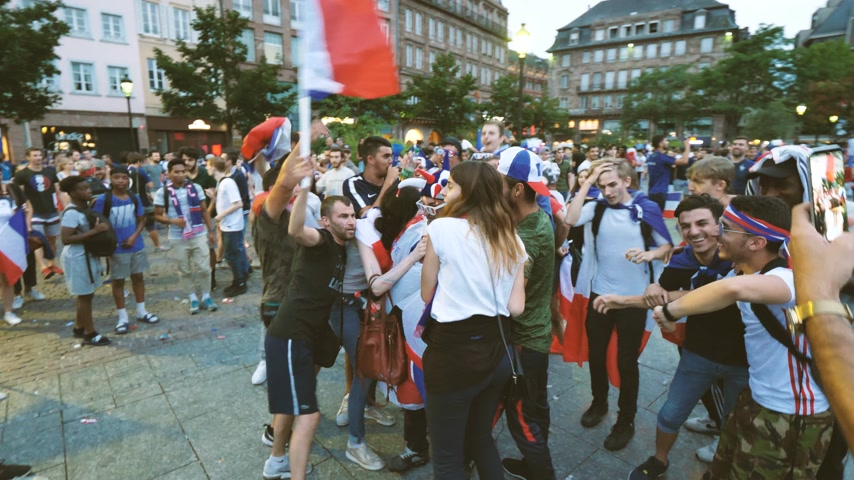 trofej : STRASBOURG, FRANCE - JULY 15, 2018: Happiness and jubilation of supporters after the victory of the French team in the final of the World Cup football man drinking Coke wearing ball costume