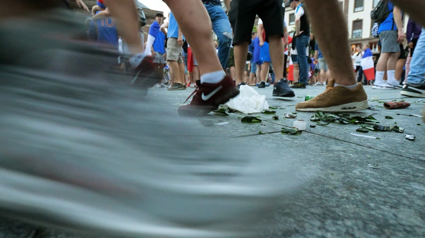 french team : STRASBOURG, FRANCE - JULY 15, 2018: Feets of people walking between broken wine and beer glass bottle after the victory of the French team in the final of the World Cup football against Croatia