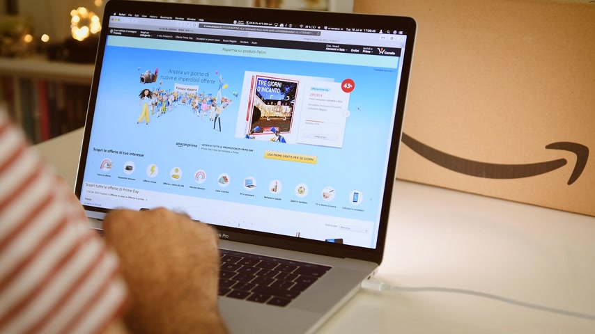 página inicial : PARIS, FRANCE - JUL 16 2019: Man POV looking at Amazon Italy Prime Day shopping deals on Apple MacBook Pro laptop with Safari Internet browser open special discounts and online consumerism shopping Stock Footage