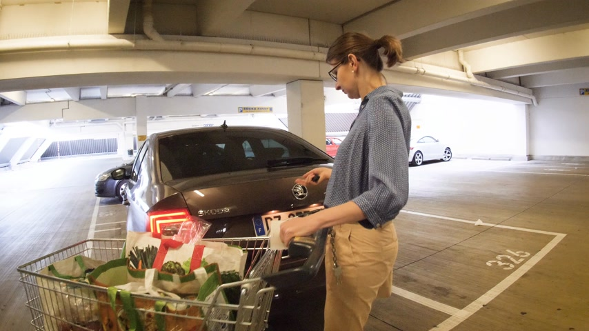 sobota : Offenburg, Germany - Circa 2017: Woman open car trunk to put groceries from shopping cart inside the car in underground Edeka Parking