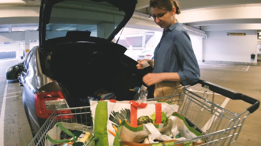 auto parking : Offenburg, Germany - Circa 2017: Woman arranging heavy bags with groceries from shopping cart inside the car in underground Edeka Supermarket Parking Stock Footage