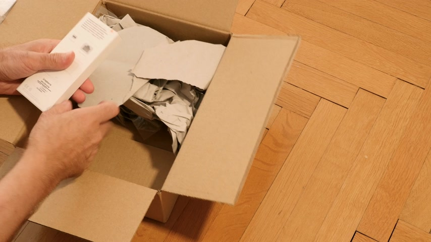 adaptador : Paris, France - Circa 2019: Male hand unboxing inspecting new Amazon Prime cardboard parcel containing new Thunderbolt to Gigabit ethernet adapter manufactured by Apple Computer