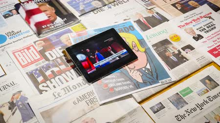 başkan : Paris, France - Jan 2017: Zoom in to multiple international newspaper featuring the election of Donald Trump as a president of United States - iPad running his and First lady dance at freedom ball Stok Video