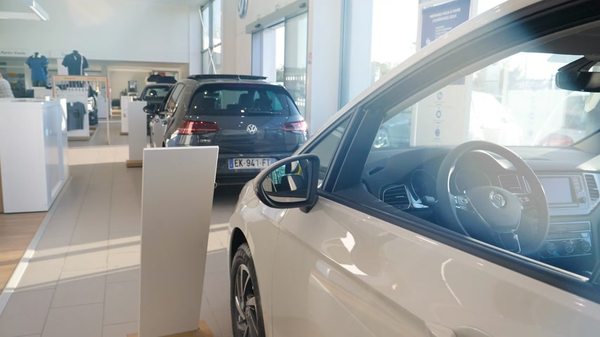 volkswagen : Strasbourg, France - Circa 2019: Sunlight flare over new Volkswagen car parked inside car dealership with multiple Golf and Polo models in background