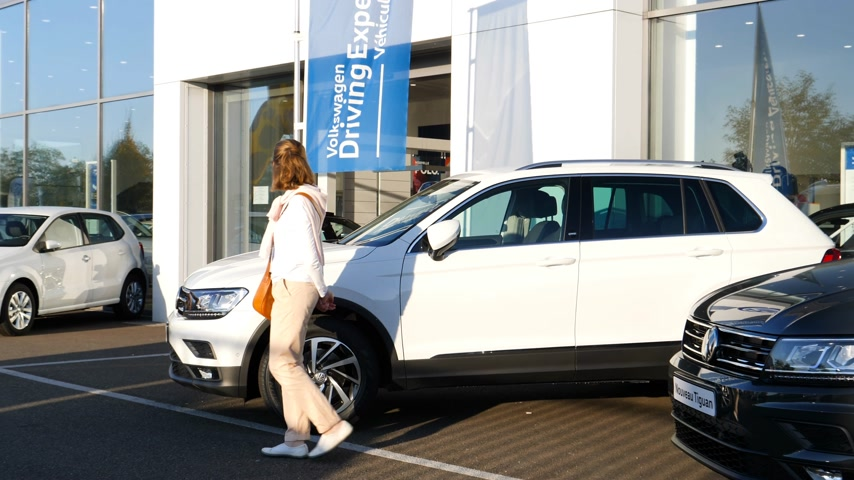 volkswagen : Strasbourg, France - Circa 2019: Rear view of young curious woman walking next to white Volkswagen Tiguan SUV car buy a new car at dealer shop