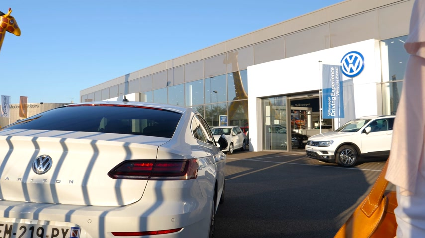 zaparkoval : Strasbourg, France - Circa 2019: Rear view of young curious woman approaching admiring new luxury white limousine white Volkswagen Arteon car buy a new car at dealer shop