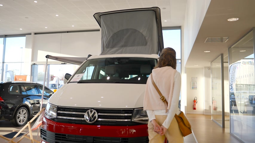 rv park : Strasbourg, France - Circa 2019: Rear view of young curious woman walking next to white and red California Camper Volkswagen RV car inside dealership Stock Footage