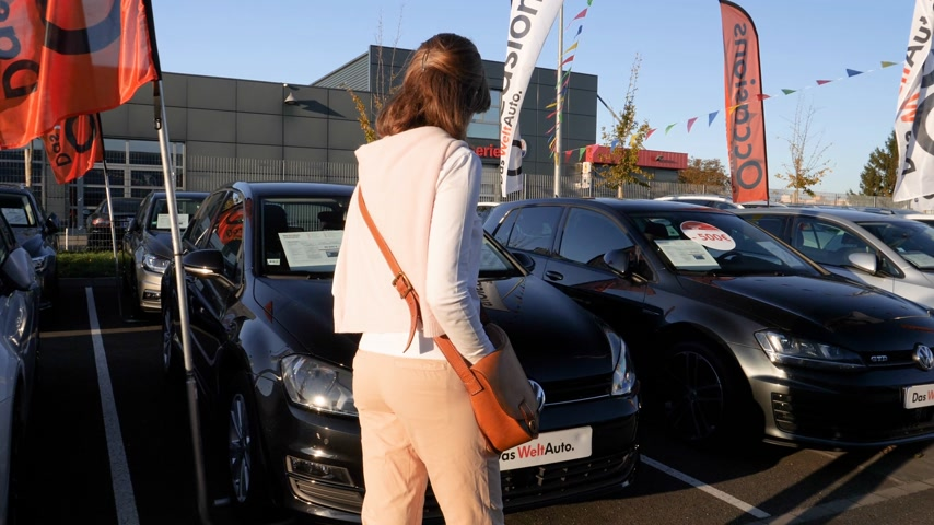 vypořádat se : Strasbourg, France - Circa 2019: Rear view of young curious woman walking between multiple Volkswagen cars buy a new car at dealer shop Das Welt