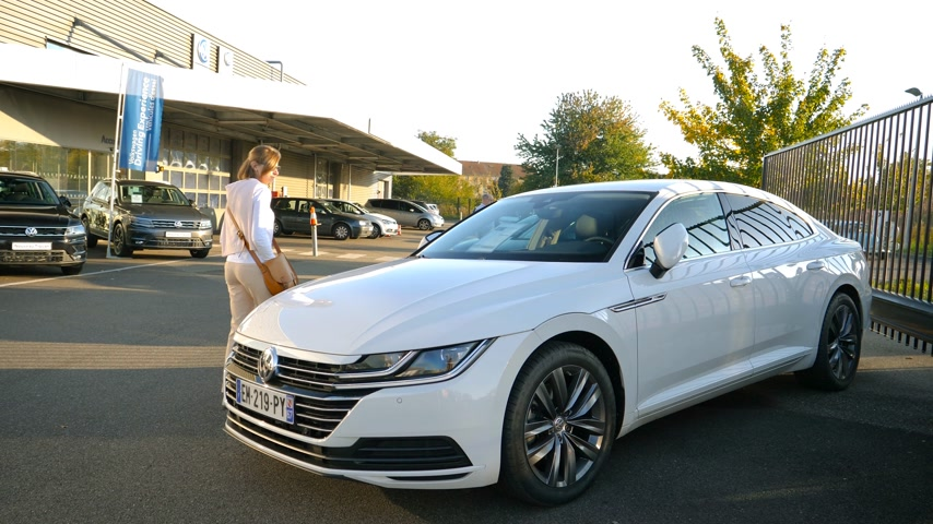 volkswagen : Strasbourg, France - Circa 2019: Elegant fashionable young curious woman approaching admiring white Volkswagen Tiguan SUV car buy a new car at dealer shop