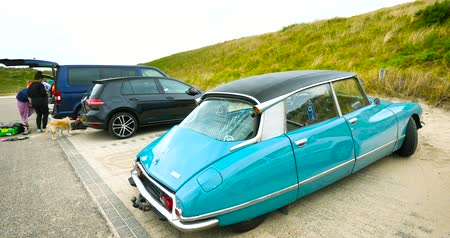 голландский : Overveen, Netherlands - Aug 16, 2019: Side view of luxury vintage old blue Citroen D Special limousine parked in the sand covered Dutch paid parking
