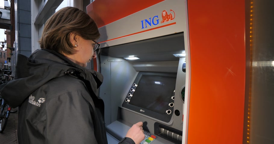 ing : Haarlem, Netherlands - Circa 2018: Time-lapse fast motion o side view of young Caucasian woman using ING Dutch bank ATM automatic teller machine to withdraw money Stock mozgókép