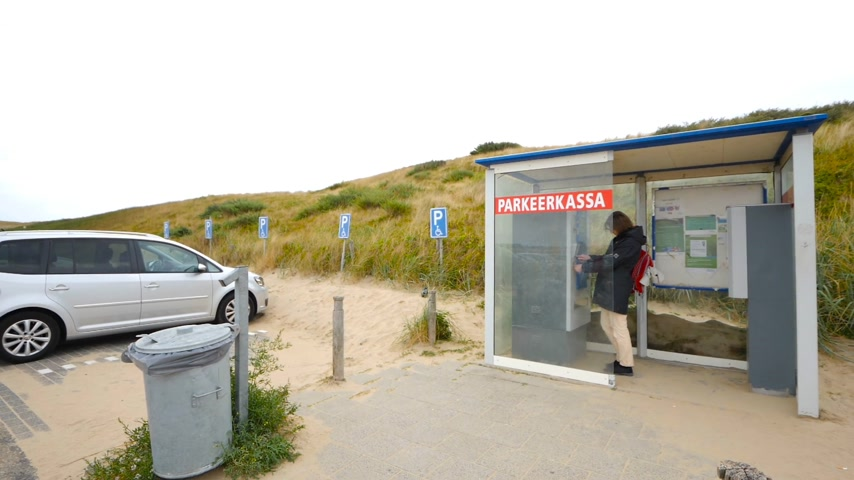 자동 판매기 : Overveen, Netherlands-2018 년경 : Parkeerkassa 주차 터미널 자동 판매기 on the sand 덮여 주차 in Netherlands Disable parking sing on the left-woman paying
