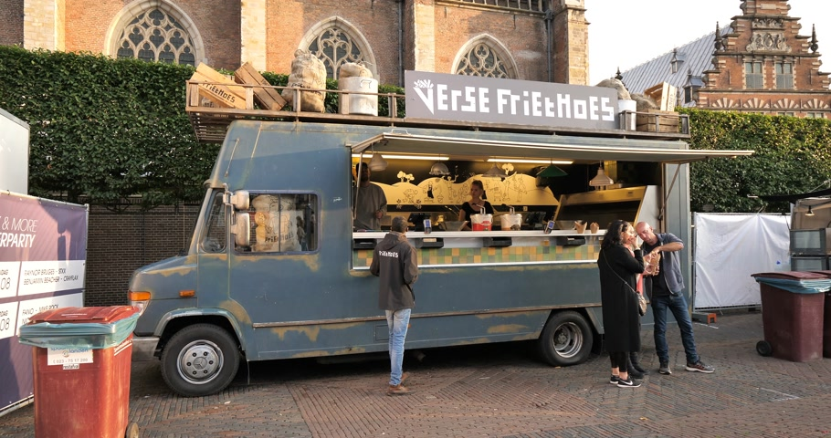 složení : Haarlem, Netherlands - Circa 2018: Food truck van selling French Fries with customers eating delicious food near The St. Bavo Church in Haarlem Dostupné videozáznamy