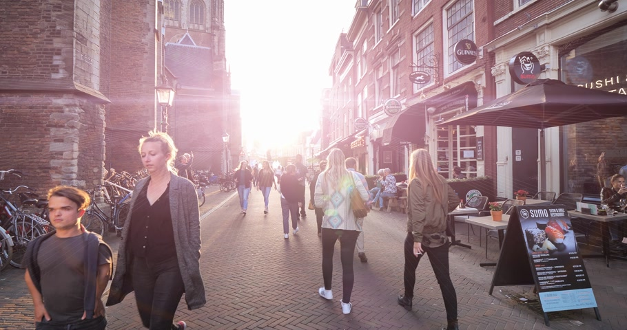 beer house : Haarlem, Netherlands - Circa 2018: Sunlight flare over St. Bavo Church in Haarlem on the left and Heineken Beer pub on the right with pedestrians walking at sunset on the Grote Markt street