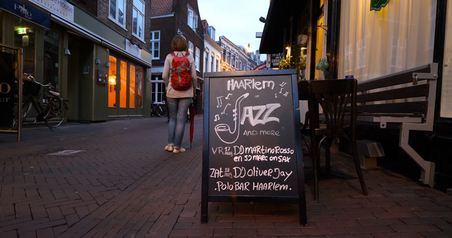 holandês : Haarlem, Netherlands - Circa 2018: Pedestrians walking at dusk on the tiny Dutch street with Haarlem Jazz and more signs advertising at the entrance of a bar pub club Stock Footage