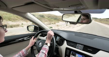 sport skoda : Overveen, Netherlands - Circa 2018: View from inside de car of woman driving a luxury Skoda Octavia through the dunes of Netherland to the Parnassia Beach