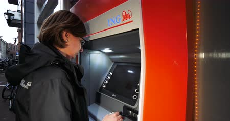 finanças : Haarlem, Netherlands - Circa 2018: Side view of young Caucasian woman using ING Dutch bank ATM automatic teller machine to withdraw money - pressing buttons on keypad Stock Footage