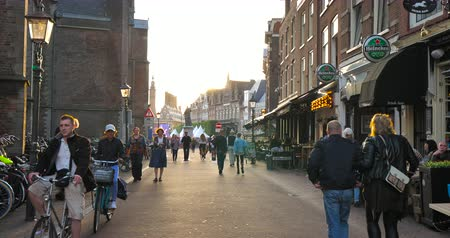 beer house : Haarlem, Netherlands - Circa 2018: The St. Bavo Church in Haarlem on the left and Heineken Beer pub on the right with pedestrians walking at sunset on the Grote Markt street