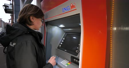 ing : Haarlem, Netherlands - Circa 2018: Side view of young caucasian woman using ING Dutch bank ATM automatic teller machine to withdraw money - insert card in slot Stock mozgókép