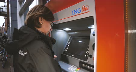 ing : Haarlem, Netherlands - Circa 2018: Side view of young caucasian woman using ING Dutch bank ATM automatic teller machine to withdraw money taking card from atm