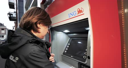 retiro de dinero : Haarlem, Netherlands - Circa 2018: Side view of young caucasian woman using ING Dutch bank ATM automatic teller machine to withdraw Euro currency money