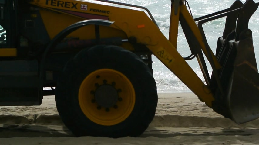 arranging : Lourinha, Portugal - Circa 2013: Yellow tractor excavator driving on the clean sand beach arranging the sand for the next beach day