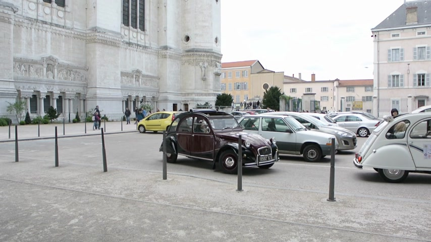 citroen : Lyon, France - Circa 2013: Two vintage Citroen 2CV driving in front of Basilique Notre-Dame de Fourviere church place Stock Footage