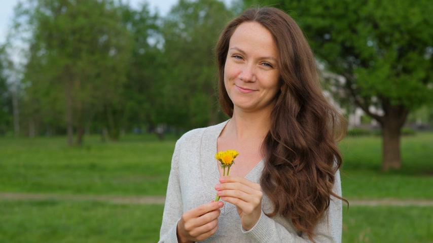 pampeliška : Woman with small dandelions in hands in countryside Dostupné videozáznamy
