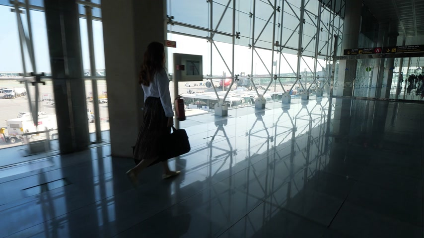 proceed : Passenger woman go in airport along glass wall., enjoy panorama of airdrome