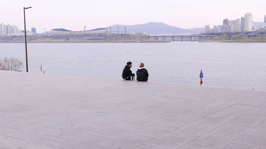 han river : Young korean couple sitting against river and Seoul city panorama